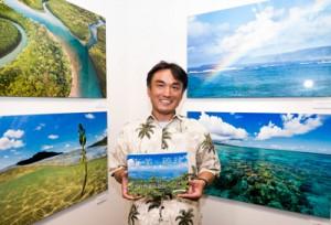 写真展会場で写真集「奄美・琉球」を手にする写真家・深澤武さん=25日 東京・中央区 銀座ニコンサロン