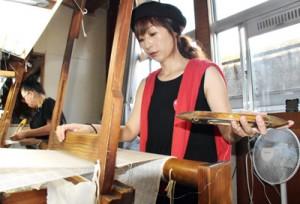 養成所で機織りを学ぶ樋渡さん=12日、鹿児島市