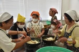 講師のアドバイスを受けて油ぞうめんの調理に取り組む参加者ら=31日、瀬戸内町古仁屋