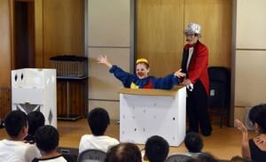 〝人体切断〟マジックで観客を驚かせた小林さん(右)=7日、奄美市住用町の役勝集会場