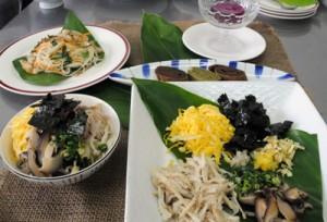 奄美の郷土料理に挑戦する参加者(上)とこの日作った料理=19日、奄美市