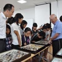 同日開催された標本名付け会・相談会で昆虫を紹介する碇山弘治さん(左)=17日、龍郷町のりゅうがく館