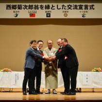 交流と協力を誓った(右から)さつま町、京都市、龍郷町、台北駐福岡経済文化辧事處、菊池市の代表=19日、龍郷町