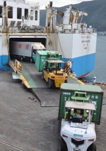 次々に運び出される食料品などを満載したコンテナと車両=24日、奄美市の名瀬港