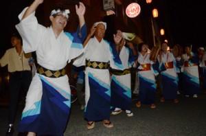そろいの浴衣姿で唄を掛け合い、八月踊りを楽しむ参加者=4日、奄美市名瀬