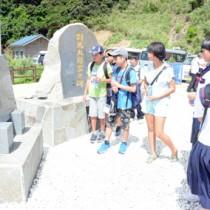 対馬丸について記された碑文を読む沖縄県と宇検村の小中学生=18日、宇検村の船越海岸
