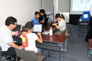 AIロボットへのプログラミングを体験する参加者ら=18日、徳之島町亀津
