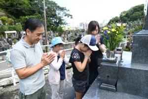 墓前で手を合わせ、先祖らの霊を自宅に伴う家族連れ=23日、奄美市名瀬の永田墓地