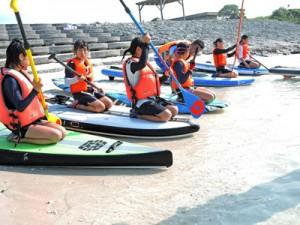SUPの練習する参加者=8日、喜界町スギラビーチ