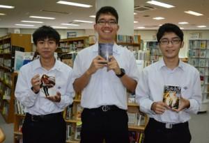 県高校生ビブリオバトル大会に出場した大島高校の(右から)保浦さん、優勝した積さん、八下田さん=20日、奄美市名瀬