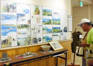 住民の話を文章入りで描いた水彩画が並ぶ証言記録展=1日、姶良市の姶良公民館