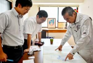 建設に関わった松元さんに話を聞く(左から)川野教諭と砂泊教諭=27日、奄美市名瀬
