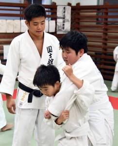 子どもたちに投げ込みを教える前山さん=28日、奄美市の名瀬公民館伊津部分館