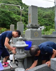 旧盆入りを前に、墓掃除に取り組む住民=22日、奄美市名瀬