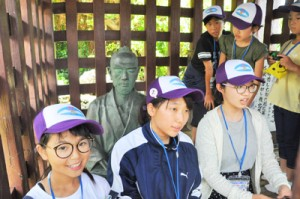 格子牢の復元施設の中で周囲を見渡したり、座禅を組んだりする児童生徒=3日、和泊町の西郷南洲記念館