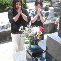 墓前で手を合わせて先祖の霊を迎える住民=13日、徳之島町
