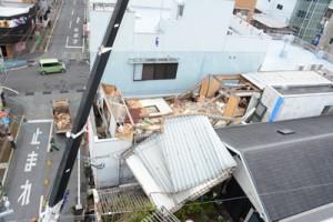 暴風で壊れ、隣接する建物を覆う商業ビルの屋根部分=22日午後2時30分ごろ、奄美市名瀬