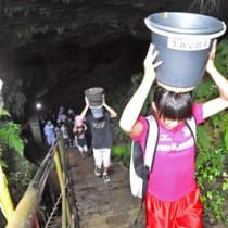地下水をバケツにくみ、階段を上がる参加者=5日、知名町の住吉クラゴー