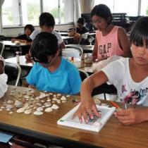 貝殻などを使って工作を楽しむ参加者=15日、奄美市笠利町