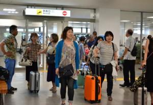 来島者と出迎えの人々でにぎわった到着ロビー=16日、奄美空港
