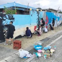壁画の修復作業を行う徳之島高校美術部の現役部員とOGら(提供写真)