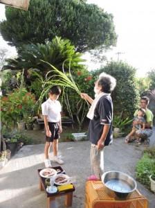 「フデーリヨ」と唱えながらススキ葉で頭をなで、子どもの成長を願うシチャミ=12日、喜界町塩道