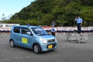 大川署長(右)や児童らに見送られパトロールに向かう青パト車両=13日、奄美市名瀬の朝日小学校