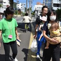 「赤ちゃん先生」を連れて育児体験を行った参加者ら=20日、奄美市名瀬