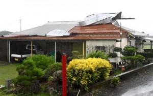 強風でトタン屋根の一部がめくれ上がった倉庫=29日午後1時50分ごろ、伊仙町伊仙