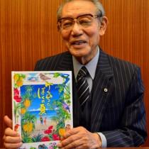 完成した絵本「ケンムンとぼくの夏」を手にする渡会長