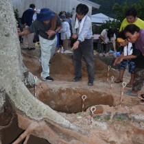 出土した人骨(左下)と住民らに説明する竹中教授(中央)=15日、宇検村屋鈍