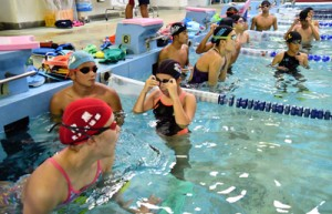 練習に励む児童生徒と全国学生選抜の選手ら=22日、名瀬運動公園屋内プール
