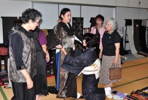 展示即売コーナーで反物を合わせて着姿をイメージする来場者ら=1日、奄美市名瀬の産業支援センター