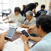 指導スタッフからタブレット、スマートフォンの操作方法を学ぶ参加者=8月30日、奄美市