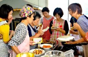 講師の福山さん(右)から調理のこつを教わる参加者=8日、奄美市名瀬