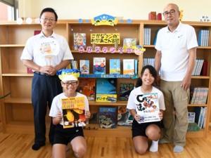 寄贈されたさかなクンの著書を手に笑みを浮かべる児童ら=6日、天城町兼久小学校