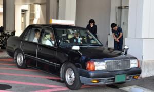 冷蔵保管された臓器を乗せ奄美空港に向かうタクシーと、見送る病院スタッフ=15日、奄美市名瀬の県立大島病院