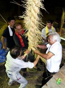 掛け声を合わせてわらを編み上げた伝統の綱かき=16日夜、伊仙町東伊仙東