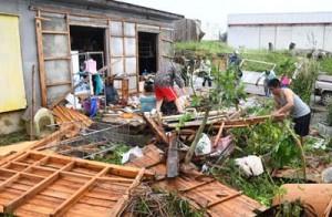 強風で被災した家を片付ける住民ら=30日午前8時50分ごろ、伊仙町面縄