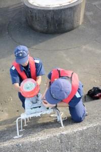 仮灯火を設置する奄美海保の職員。後方にある円形の土台が消失灯台のあった場所=6日、奄美市の名瀬港西防波堤