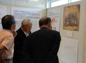 大正時代に村で撮影された貴重な写真に見入る企画展開幕式の出席者=22日、宇検村の元気の出る館