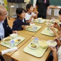 竹田町長(左)と地場産米を使った給食を味わう秋名小児童ら=11日、龍郷町
