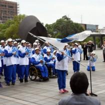 結団式で県旗を受け取る選手=11日、鹿児島市の県庁