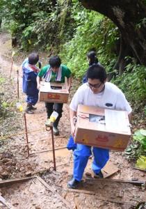 住民の購入品を持って避難用歩道を上る奄美市の職員=4日、奄美市名瀬小浜町