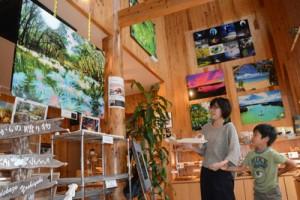 店内に展示した写真を観賞する利用客=15日、奄美市名瀬の「夢来夢来」