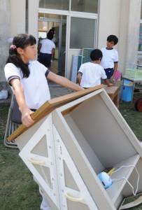 浸水した校舎の片付けに追われる諸鈍校の児童生徒=1日午後2時ごろ、瀬戸内町諸鈍