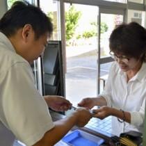 商品券を購入する女性(右)=22日、龍郷町瀬留の町商工会