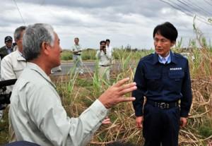 サトウキビの被害状況などについて説明を受ける三反園訓知事(右)=12日、奄美市笠利町