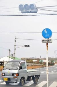停電で信号が消えた交差点を慎重に通る車=4日、和泊町