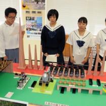 製作した復元模型を前に、久慈の白糖製造工場について説明する生徒=22日、瀬戸内町の県立古仁屋高校